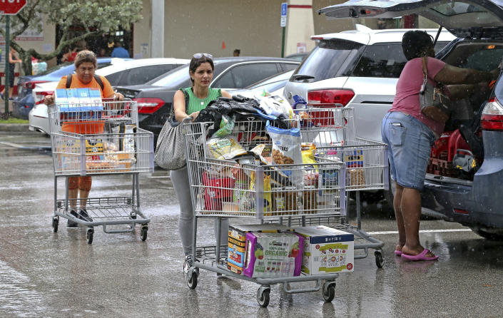 Shoppers race to their cars in the rain after shopping at Costco as they prepare for Hurricane Dorian, Friday, Aug. 30, 2019 in Davie, Fla. Hurricane Dorian was muscling a chaotic path toward Florida, with officials and residents bracing for the possibility it would unleash its full fury early next week but clinging to the glimmer of hope that the strengthening storm could simply skirt the coastline. (Charles Trainor, Jr./Miami Herald via AP)