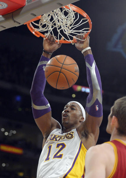 Los Angeles Lakers center Dwight Howard dunks as Cleveland Cavaliers center Tyler Zeller watches during the first half of an NBA basketball game, Sunday, Jan. 13, 2013, in Los Angeles. (AP Photo/Mark J. Terrill)