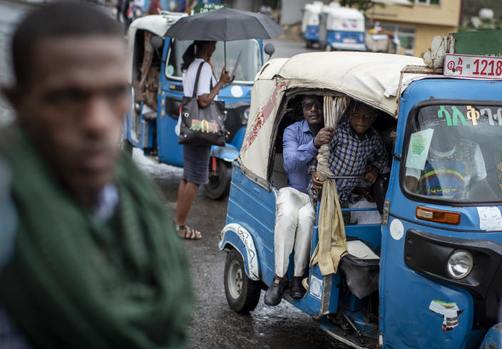 """Passengers look out from an auto-rickshaw, known locally as a """"bajaj"""", in Gondar, in the Amhara region of Ethiopia Sunday, May 2, 2021. Ethiopia faces a growing crisis of ethnic nationalism that some fear could tear Africa's second most populous country apart, six months after the government launched a military operation in the Tigray region to capture its fugitive leaders. (AP Photo/Ben Curtis)"""