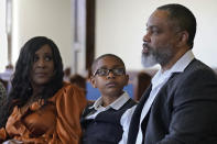 LeRoy Gibbs II, right, grandson of Tulsa Race Massacre survivor Ernestine Alpha Gibbs, speaks during an interview Sunday, April 11, 2021, in Tulsa, Okla., accompanied by his wife, Tracy Gibbs, left, and son, LeRoy Gibbs III. The family's Gibbs Next Generation Center, a small shopping mall and office park, used to be the location of businesses run by LeRoy II's grandfather and grandmother. (AP Photo/Sue Ogrocki)