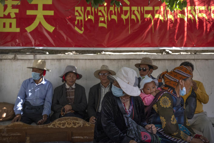 People rest in the shade beneath a government propaganda banner in Chinese and Tibetan near a neighborhood Tibetan Buddhist shrine in the Chengguan district of Lhasa in western China's Tibet Autonomous Region, as seen during a rare government-led tour of the region for foreign journalists, Thursday, June 3, 2021. Long defined by its Buddhist culture, Tibet is facing a push for assimilation and political orthodoxy under China's ruling Communist Party. (AP Photo/Mark Schiefelbein)