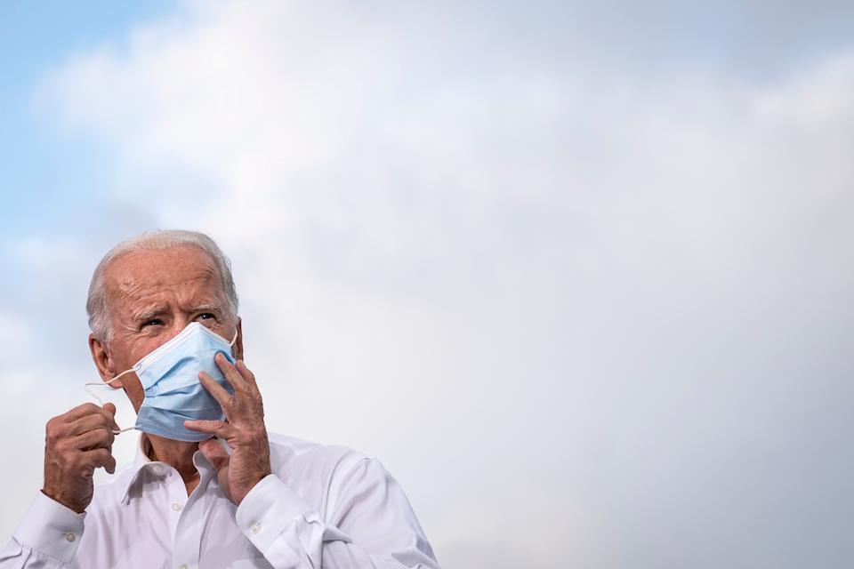 <p>Joe Biden removes his mask during a campaign event.</p>Getty Images