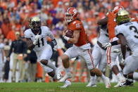 Clemson quarterback Trevor Lawrence (16) scrambles out of the pocket while defended by Wake Forest's Ja'Corey Johns (41) Clemson's during the first half of an NCAA college football game Saturday, Nov. 16, 2019, in Clemson, S.C. (AP Photo/Richard Shiro)