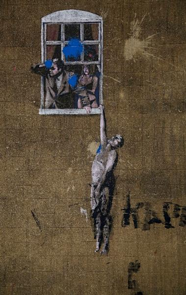 "Banksy's street art, titled ""Well Hung Lover"" in Bristol, is another popular stop for tourists (AFP Photo/GEOFF CADDICK)"