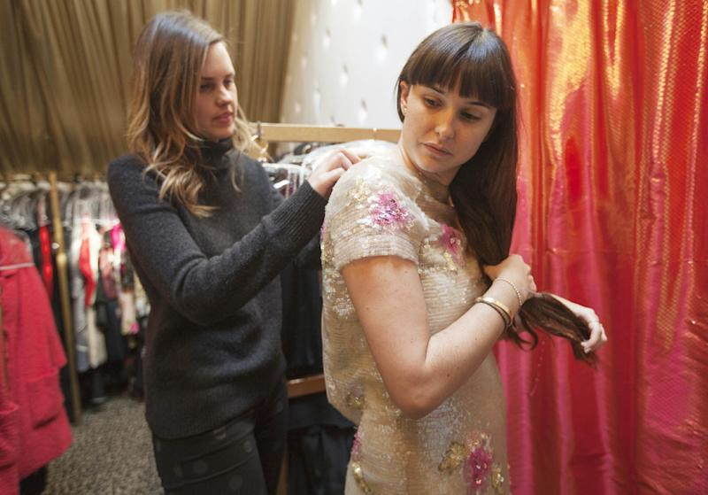 """In this photo taken Thursday, Feb. 21, 2013, Angelika Sjostrom, left, helps antique jewelry dealer, Hilary Tisch, to try on a vintage sequin dress at """"The Way We Wore,"""" Hollywood's high-end vintage store owned by Doris Raymond in Los Angeles. The vintage clothing and accessories store is featured in the reality TV series, """"L.A. Frock Stars,"""" which debuts March 7, 2013 on the Smithsonian Channel. (AP Photo/Damian Dovarganes)"""