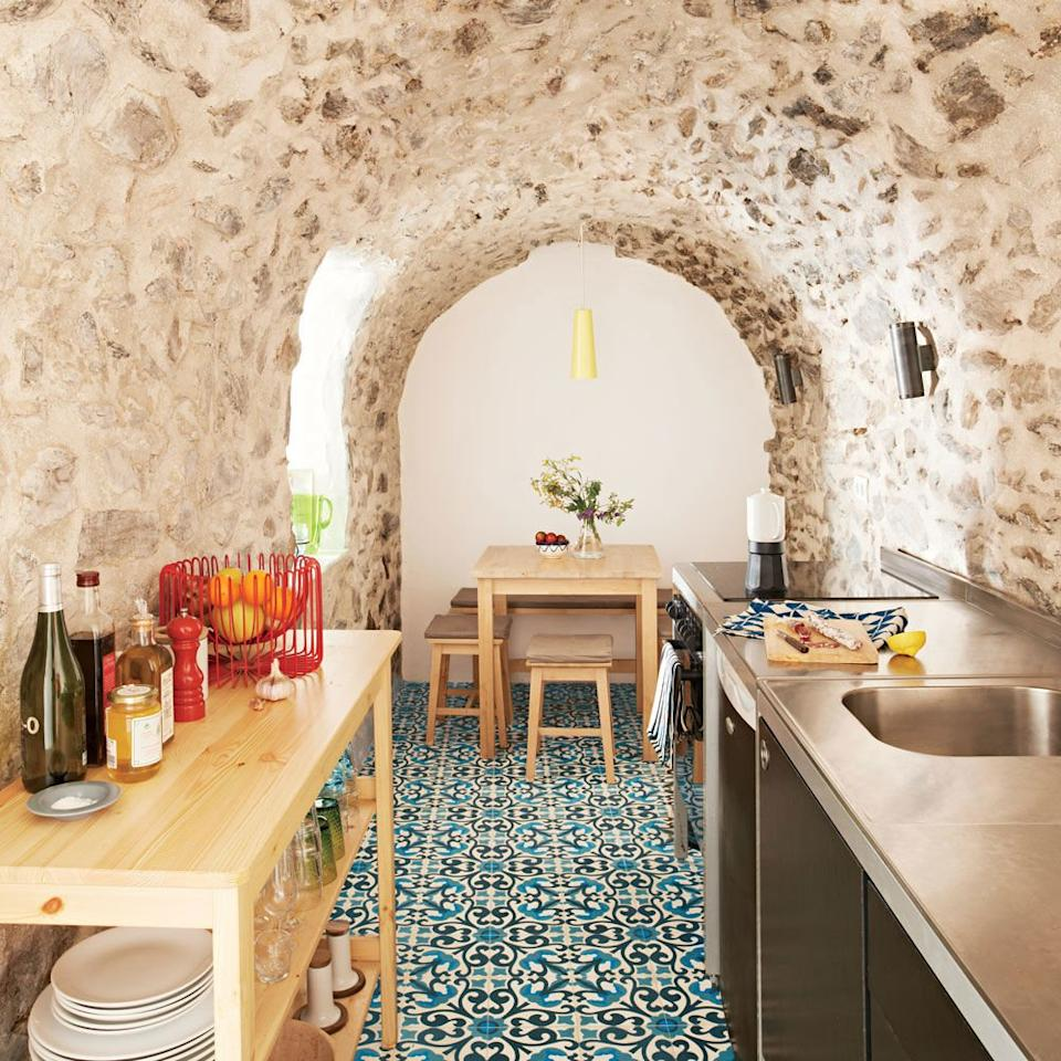 <p>Rather than force traditional upper cabinetry in this centuries-old Spanish kitchen (the entire home is only 460 square feet!), the owners left the stone archway untouched. They implemented small modular furniture and appliances down each side of the narrow cook space, resulting in an earthy kitchen with character and efficiency.</p>