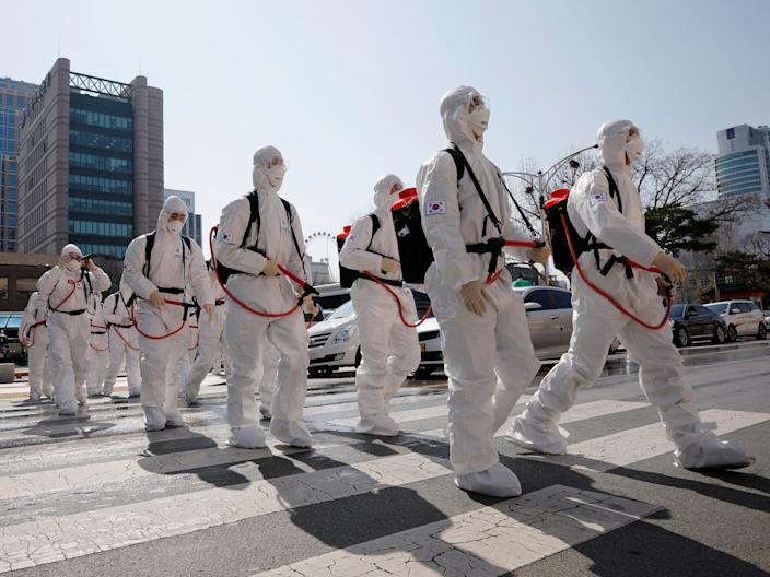 South Korean soldiers wearing protective gear walk on a street in front of Daegu's city hall after a rapid rise in cases of the coronavirus, March 2, 2020.