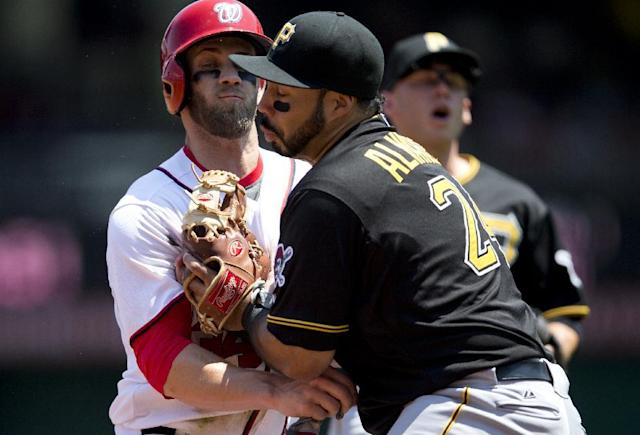Washington Nationals Bryce Harper, left, left, collides with Pittsburgh Pirates third baseman Pedro Alavarez, center, as Pirates shortstop Clint Barmes looks on during the first inning of a baseball game at Nationals Park on Thursday, July 25, 2013, in Washington. Harper scored on the play as Alvarez was charged with an error for dropping the throw from Barmes. (AP Photo/Evan Vucci)