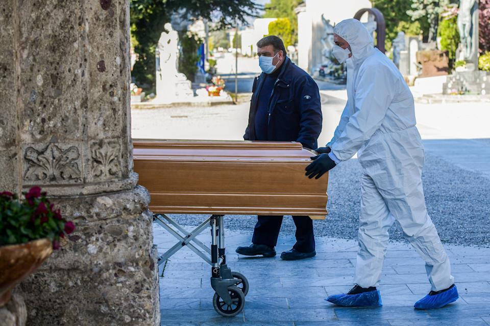 TOPSHOT - An undertaker wearing a face mask and overalls unloads a coffin out of a hearse on March 16, 2020 at the Monumental cemetery of Bergamo, Lombardy, as burials of people who died of the new coronavirus are being conducted at the rythm of one every half hour. (Photo by Piero Cruciatti / AFP) (Photo by PIERO CRUCIATTI/AFP via Getty Images)