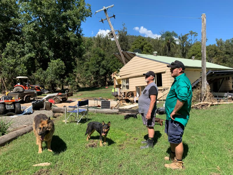 Australia cattle farmer Robert Costigan and his father-in-law Brian Watt stand in front of Watt's home that got swept off its foundations by floodwater and into a telegraph pole on the property in Hollisdale, Australia