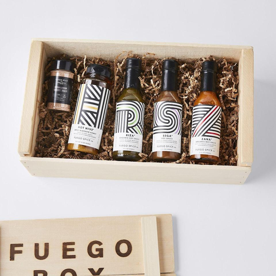 """<p><strong>Fuego Box</strong></p><p>food52.com</p><p><strong>$59.95</strong></p><p><a href=""""https://go.redirectingat.com?id=74968X1596630&url=https%3A%2F%2Ffood52.com%2Fshop%2Fproducts%2F8510-hot-sauce-eco-gift-crate&sref=https%3A%2F%2Fwww.menshealth.com%2Ftechnology-gear%2Fg36434010%2Fhot-sauce-gifts%2F"""" rel=""""nofollow noopener"""" target=""""_blank"""" data-ylk=""""slk:BUY IT HERE"""" class=""""link rapid-noclick-resp"""">BUY IT HERE</a></p><p>Food52 is selling a fancy little hot sauce gift basket for Father's Day that will plant five trees for every crate sold. Inside you'll find hot sauce that will upgrade any cookout (thanks to the packaging alone), while offering a diverse profile that offers a classic red, punchy verde, and a vinegary Carolina Reaper. To offset the heat, you'll also find Ghost-Pepper infused Himalayan pink salt and a spicy take on hot honey. It's the ultimate hot-sauce centered gourmet gift.</p>"""