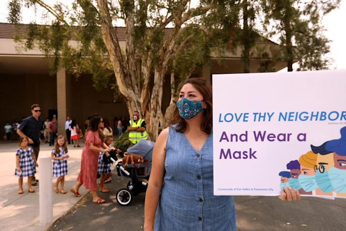 A woman holds a sign that says Love thy neighbor and wear a mask