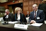 Members of the Croatian delegation, Minister Orsat Miljenic, right, Vesna Crnic-Grotic, center, and James Crawford, left, during the start of public hearings at the International Court of Justice (ICJ) in The Hague, Netherlands, Monday, March 3, 2014. Croatia is accusing Serbia of genocide during fighting in the early 1990's as the former Yugoslavia shattered in spasms of ethnic violence, in a case at the United Nations' highest court that highlights lingering animosity in the region. Croatia is asking the ICJ to declare that Serbia breached the 1948 Genocide Convention when forces from the former Federal Republic of Yugoslavia attempted to drive Croats out of large swaths of the country after Zagreb declared independence in 1991. (AP Photo/Jiri Buller)