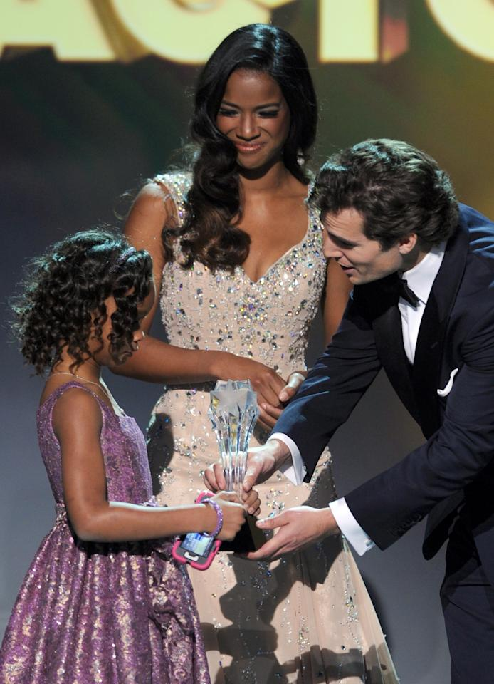 "SANTA MONICA, CA - JANUARY 10:  Actor Henry Cavill (R) presents actress Quvenzhane Wallis the Best Young Actor/Actress Award for ""Beasts of the Southern Wild"" onstage at the 18th Annual Critics' Choice Movie Awards held at Barker Hangar on January 10, 2013 in Santa Monica, California.  (Photo by Kevin Winter/Getty Images)"