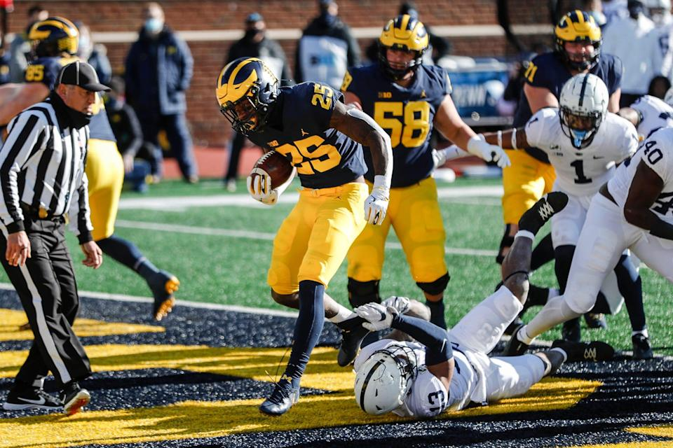 Michigan running back Hassan Haskins jumps over Penn State linebacker Ellis Brooks for a touchdown during the first half at Michigan Stadium in Ann Arbor, Saturday, Nov. 28, 2020.