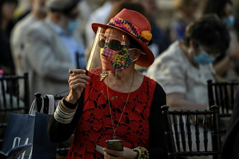 A spectator wearing a face mask and visor attends the concert