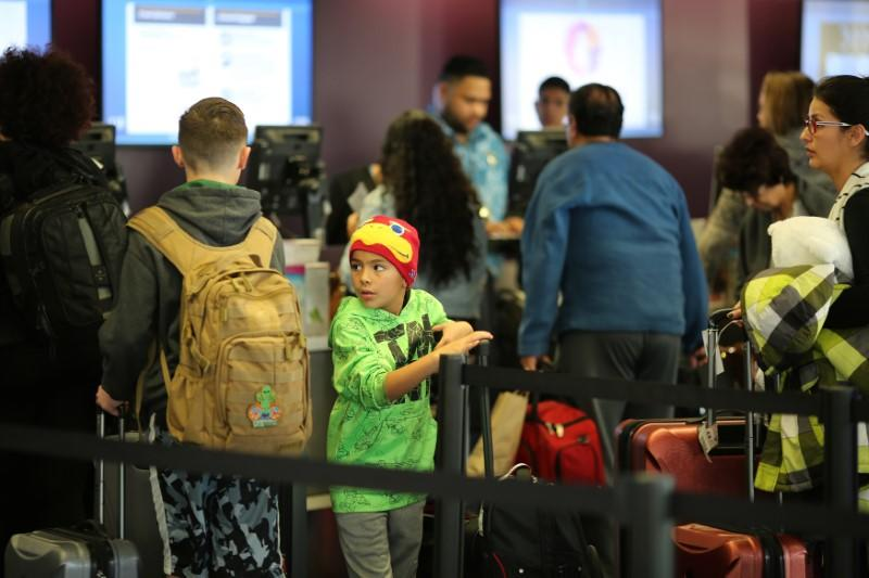 Travelers pass through Los Angeles International Airport (LAX) on the day before Thanksgiving in Los Angeles