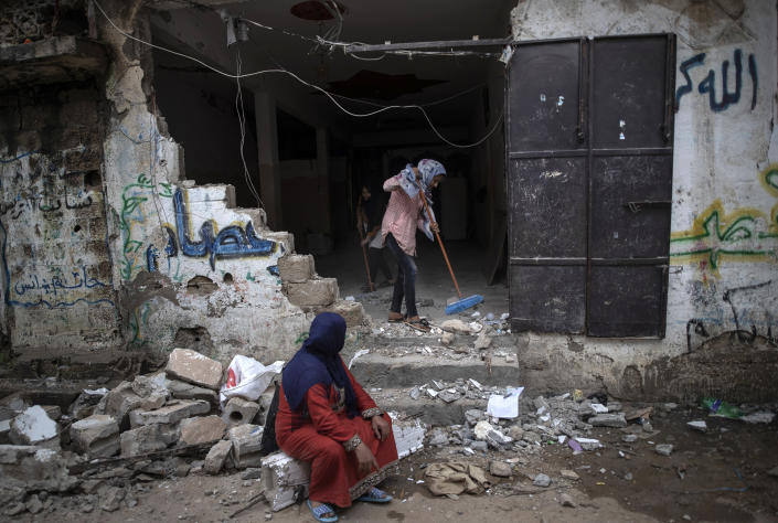 A Palestinian family remove the rubble from their damaged home following a cease-fire reached after an 11-day war between Gaza's Hamas rulers and Israel, in town of Beit Hanoun, northern Gaza Strip, Friday, May 21, 2021. (AP Photo/Khalil Hamra)