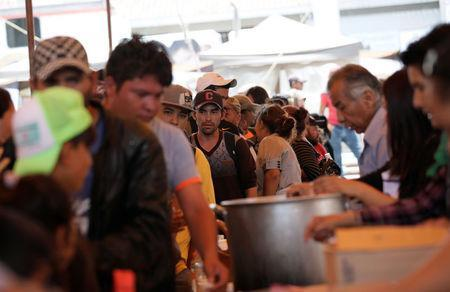 Central American migrants moving in a caravan through Mexico toward the U.S. border, stand in line for food at a shelter set up for them by the Catholic church, in Puebla, Mexico April 6, 2018. REUTERS/Henry Romero