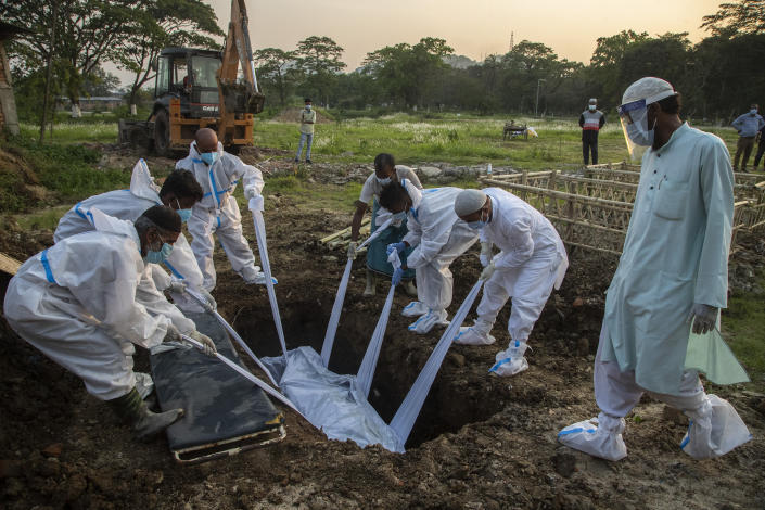 Relatives and municipal workers in protective suit bury the body of a person who died due to COVID-19 in Gauhati, India, Sunday, April 25, 2021. Delhi has been cremating so many bodies of coronavirus victims that authorities are getting requests to start cutting down trees in city parks, as a second record surge has brought India's tattered healthcare system to its knees. (AP Photo/Anupam Nath)