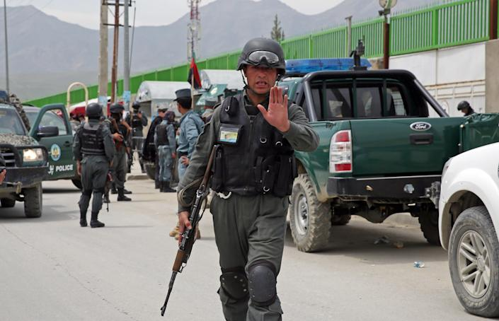 An Afghan policeman prevents journalists from approaching Cure International Hospital in Kabul, Afghanistan, Thursday, April 24, 2014. The U.S. embassy in Afghanistan says three American doctors have been killed at by an Afghan security guard who opened fire at a hospital in Kabul. The shooting at Cure International Hospital in western Kabul was the latest attack on foreign civilians in the Afghan capital this year. (AP Photo/Massoud Hossaini)