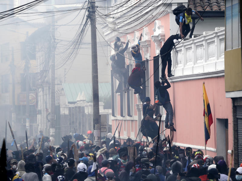 Anti-government demonstrators scale the facade of a residence to reach the rooftop, looking for a better vantage point to battle with police, in Quito, Ecuador, Friday, Oct. 11, 2019. Protests, which began when President Lenin Moreno's decision to cut subsidies led to a sharp increase in fuel prices, persisted for days. (AP Photo/Dolores Ochoa)