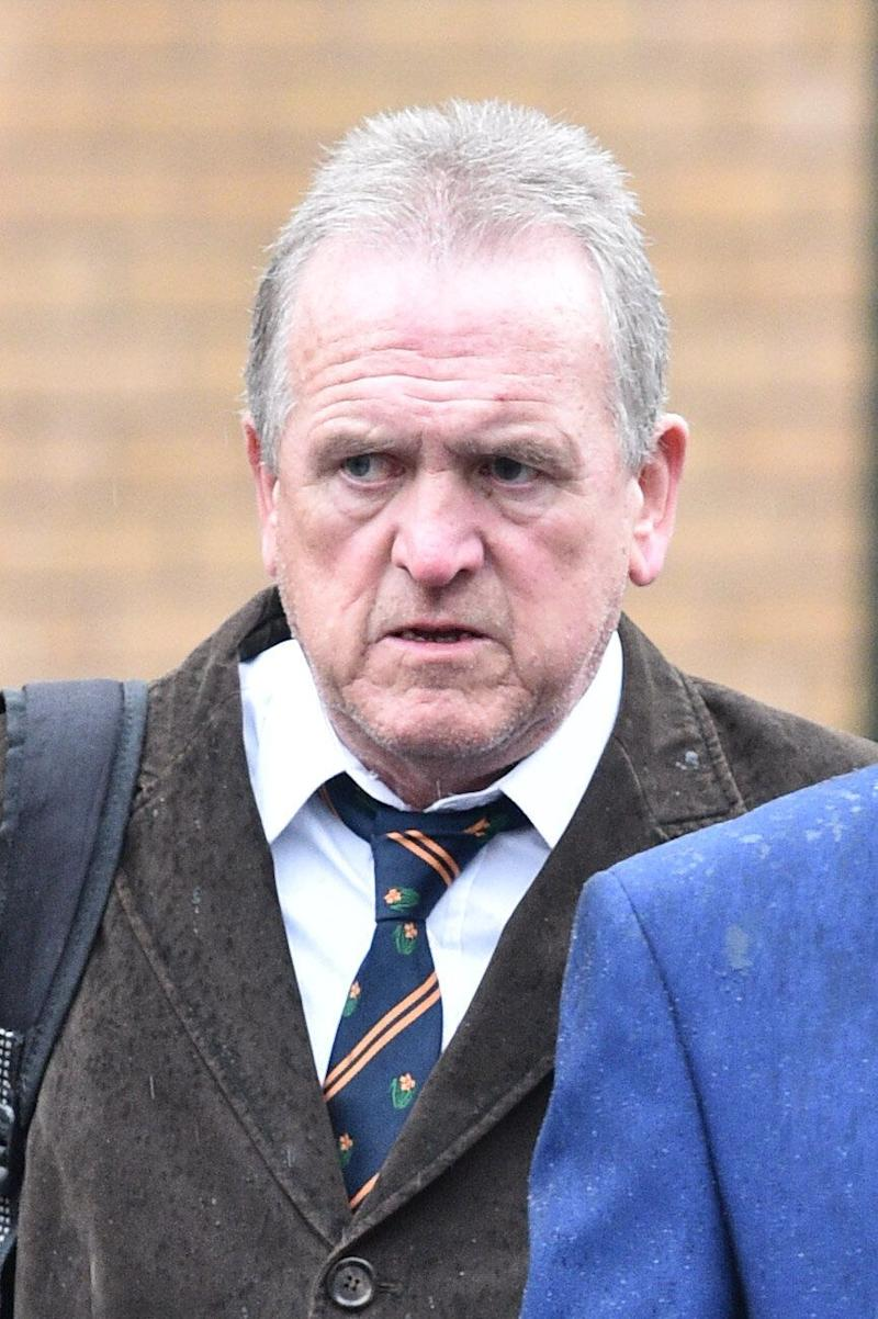 Brian Davies, 62, leaves Cardiff Magistrates' Court where he denies charges of causing racially aggravated harassment, alarm or distress. Mr Davies is alleged to have dressed up as a black and white minstrel during a works party and sang in the face of a black employee to mock her.