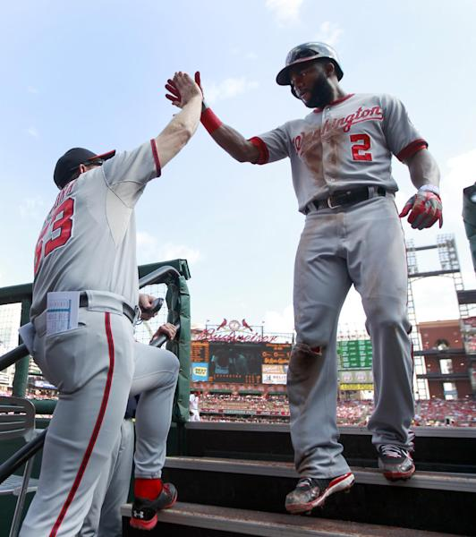 Washington Nationals' Denard Span, right, is congratulated by bench coach Randy Knorr after scoring on a single by Bryce Harper during the first inning of a baseball game against the St. Louis Cardinals Wednesday, Sept. 25, 2013, in St. Louis. (AP Photo/Jeff Roberson)