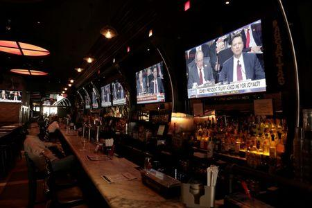 A man watches a television showing former FBI director James Comey's testimony before the Senate Intelligence Committee, in Tonic bar in New York City