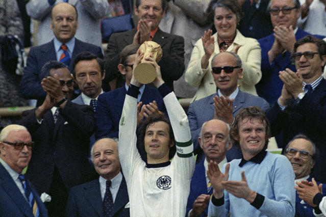FILE - In this July 7, 1974 file photo, West Germany captain, Franz Beckenbauer holds up the World Cup trophy after his team defeated the Netherlands 2-1, in the World Cup soccer final at Munich's Olympic stadium, in West Germany. Once again, Germany dug deep Saturday, June 23, 2018 to eke out a victory to keep its World Cup hopes alive. It's something German teams have made a habit of at World Cups. (AP Photo/File)