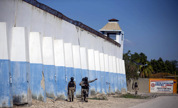 National police officers search for inmates on the perimeters of the Croix-des-Bouquets Civil Prison in Port-au-Prince, Haiti, Thursday, Feb. 25, 2021. At least seven people were killed and one injured on Thursday after eyewitnesses told The Associated Press that several inmates tried to escape from the prison in Haiti's capital. (AP Photo/Dieu Nalio Chery)