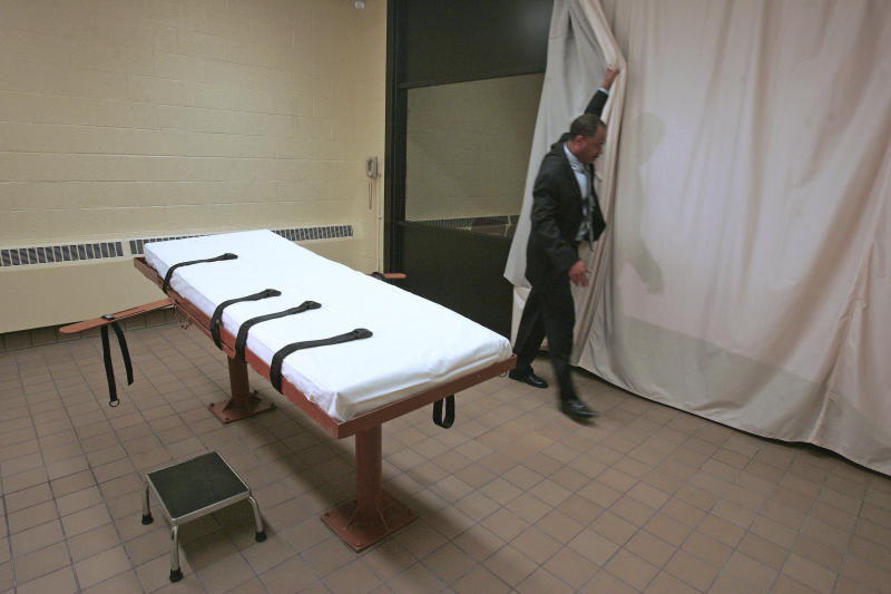FILE – In this November 2005 file photo, Larry Greene, public information director of the Southern Ohio Correctional Facility, demonstrates how a curtain is pulled between the death chamber and witness room at the prison in Lucasville, Ohio. The effectiveness of midazolam has been questioned following executions in Ohio, Arizona and, in April 27, 2017, Arkansas. Condemned inmate Kenneth Williams lurched and convulsed 20 times during a lethal injection execution that began with the controversial drug. (AP Photo/Kiichiro Sato, File)