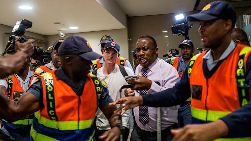 The plain-clothed Steve Smith was ushered through Johannesburg's international airport. Pic: Getty