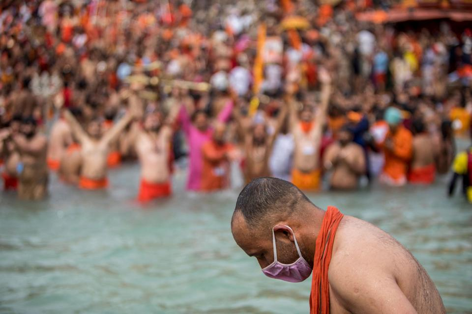 TOPSHOT - A Sadhu wearing a facemask takes a holy dip in the Ganges river during the ongoing religious Kumbh Mela festival in Haridwar on April 12, 2021. (Photo by Xavier GALIANA / AFP) (Photo by XAVIER GALIANA/AFP via Getty Images)