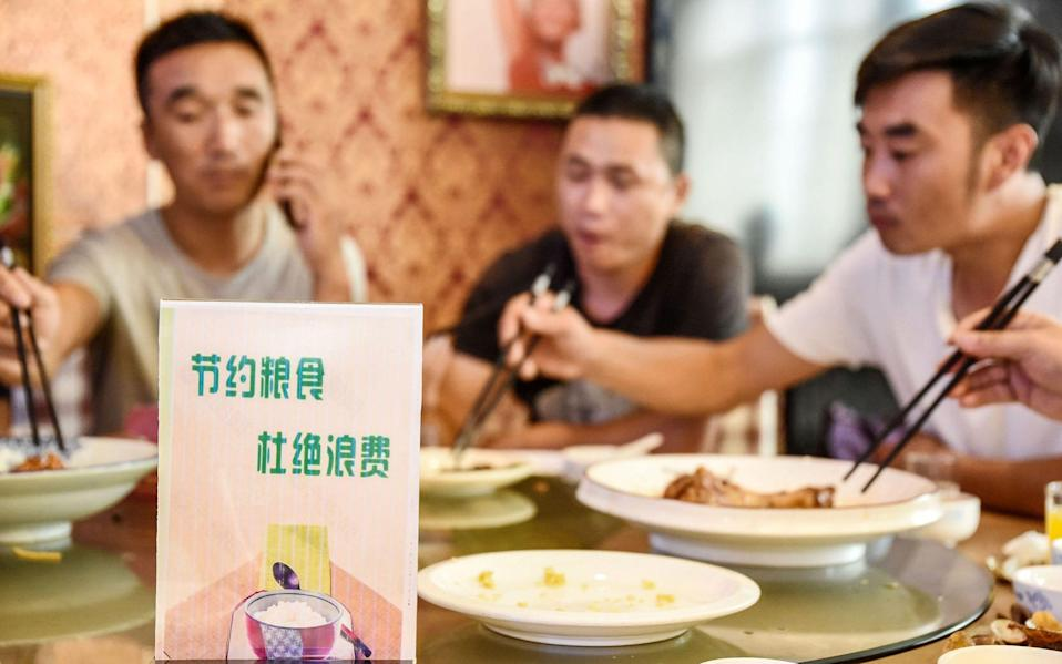 "A sign encouraging people not to waste food is seen at a restaurant in Handan. Chinese diners are being urged to order ""one less plate"", after Chinese President Xi Jinping made a speech urging the nation to stop wasting food - STR/AFP"