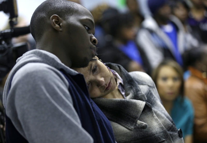 Adrean Bennett, brother of victim Andrique Bennett, and Charlene Blackwell hug during a prayer meeting Monday, March 11, 2013, in Warren, Ohio. Victim Raymone White is Blackwell's nephew. Community members crowded into a prayer service to remember six teens killed when an SUV flipped over a guardrail and landed upside down in a pond. (AP Photo/Tony Dejak)