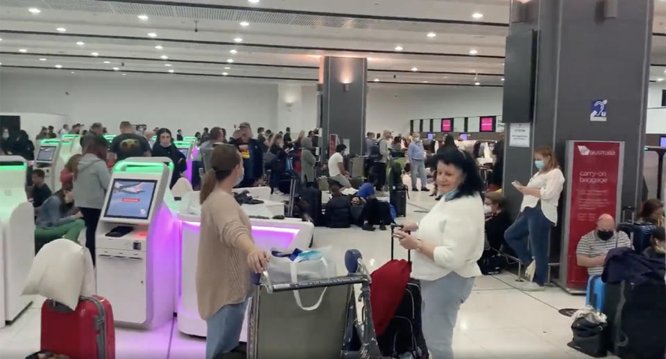 Travellers wait in queues and find seating on the floor while they wait for the airline's issue to be resolved.