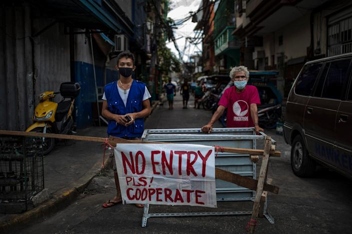 Angel Navarro and Nonoy Zapanta pose for a portrait as they guard a makeshift barricade blocking one of the entrances to Barangay 46 to prevent the spread of COVID-19 in their village on March 20, 2020 in Manila, Philippines.
