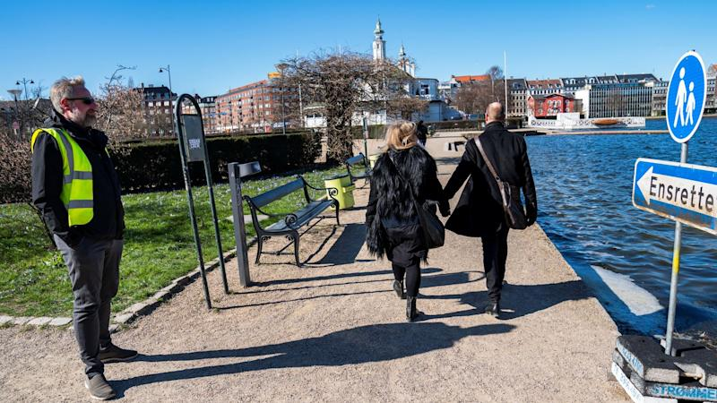 A park warden helps direct pedestrians in Copenhagen
