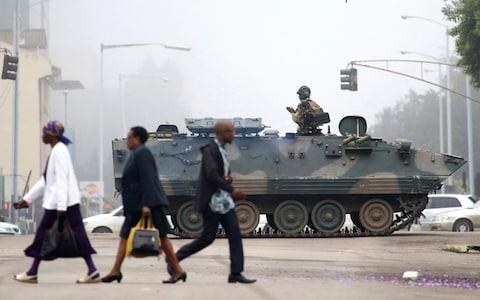 Armoured personnel carriers are stationed at major junctions in Harare as residents attempt to continue with their daily lives under the spectre of an alleged coup - Credit: AP