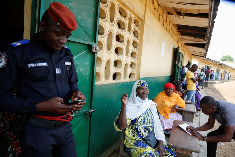 People wait for the opening of a polling station during the legislative election in Abidjan
