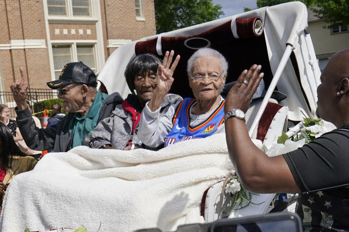 Tulsa race massacre survivors Hughes Van Ellis Sr., left, Lessie Benningfield Randle, center, and Viola Fletcher, right, wave and high-five supporters from a horse drawn carriage before a march Friday, May 28, 2021, in Tulsa, Okla. (AP Photo/Sue Ogrocki)