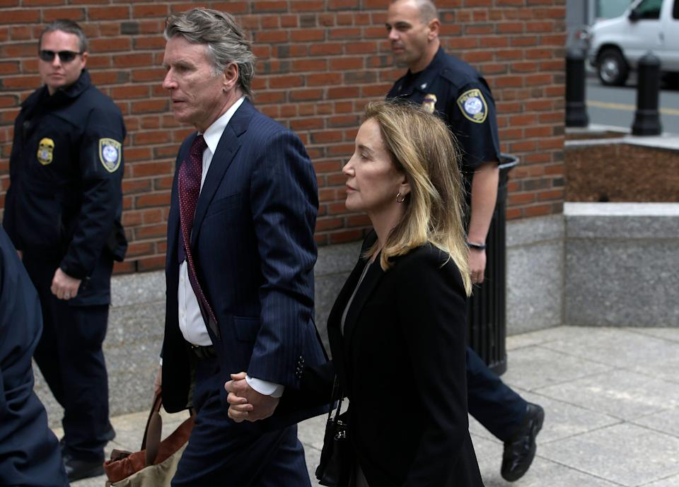 Felicity Huffman arrives with her brother Moore Huffman Jr., at federal court Monday, May 13, 2019, in Boston, where she is scheduled to plead guilty to charges in a nationwide college admissions bribery scandal. (AP Photo/Steven Senne)