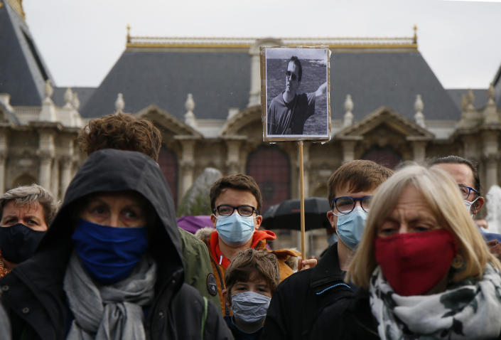A person holds up a a portrait of Samuel Paty as they gather on Republique square in Lille, northern France, Sunday Oct. 18, 2020. Demonstrators in France on Sunday took part in gatherings in support of freedom of speech and in tribute to a history teacher who was beheaded near Paris after discussing caricatures of Islam's Prophet Muhammad with his class. (AP Photo/Michel Spingler)