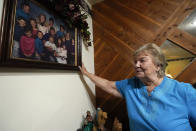 Frances Sims, looks over a family photo at her home Tuesday, Aug. 10, 2021, in Hilliard, Fla. Although some of her family members have been vaccinated Sims remains unshaken in her decision not to get a coronavirus shot. (AP Photo/John Raoux)