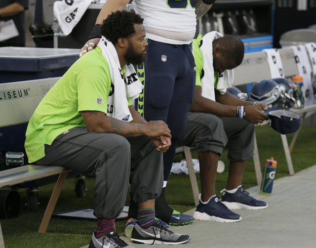 Michael Bennett (in foreground) remains seated during the national anthem. (AP)