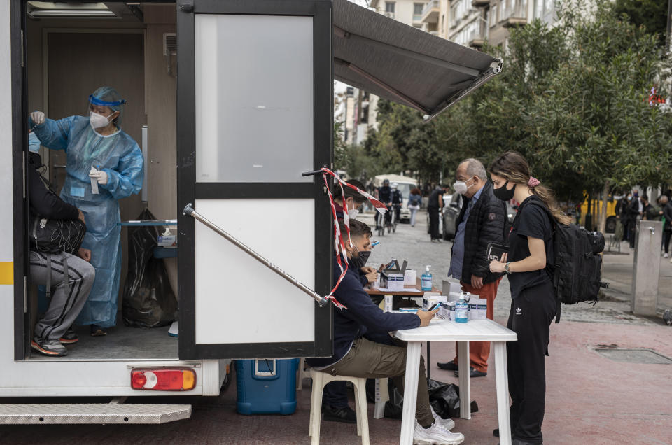A medical staff of the National Health Organisation (EODY) conducts a rapid test for the COVID-19, in Ermou street, central Athens, on Monday, April 5, 2021. Retail stores across most of Greece have been allowed to reopen despite an ongoing surge in COVID-19 infections, as the country battled to emerge from deep recession.(AP Photo/Petros Giannakouris)