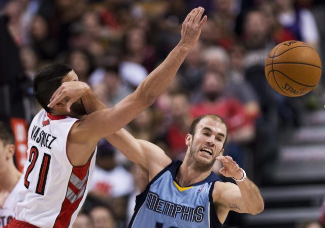 Toronto Raptors guard Greivis Vasquez, left, battlesd for the loose ball against Memphis Grizzlies guard Nick Calathes, right, during first half NBA basketball action in Toronto on Friday, March. 14, 2014. (AP Photo/The Canadian Press, Nathan Denette)