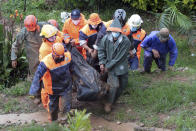 Rescuers carry the body of a victim caught in a landslide caused by Tropical Storm Kompasu in Baguio city, northern Philippines on Tuesday Oct. 12, 2021. A number of people have been killed and others were reported missing in landslides and flash flood set off by a storm that barreled through the tip of the northern Philippines overnight then blew away Tuesday, officials said. (AP Photo)