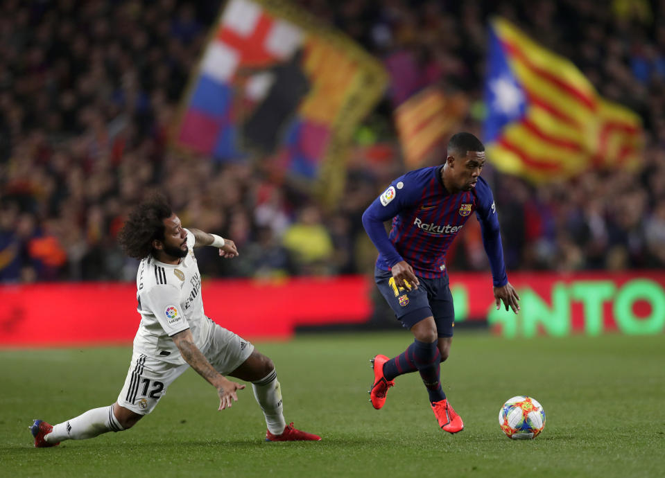 """FILE - In this Feb. 6, 2019 file photo, Barcelona forward Malcom, right, and Real's Marcelo run for the ball in front of an Estelada or pro-independece flag during the Copa del Rey semifinal first leg soccer match between FC Barcelona and Real Madrid at the Camp Nou stadium in Barcelona, Spain. Next week's """"clsico"""" between Barcelona and Real Madrid, due to be played on Oct. 26, 2019, has been postponed by the Spanish soccer federation to avoid coinciding with a large separatist rally in riot-stricken Catalonia. The federation's competitions committee says Barcelona and Madrid have until Monday to decide on another date. (AP Photo/Manu Fernandez, File)"""
